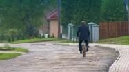 Mężczyzna jadący rowerem wiejską drogą