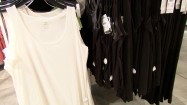 Białe i czarne koszulki na wieszakach