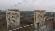 Bloki mieszkalne na tle dymiących kominów