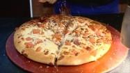 Posypywanie pizzy parmezanem