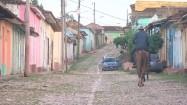 Mężczyźni jadący uliczką na koniach