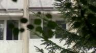 Budynek z balkonami - widok zza drzew