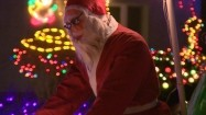 Św. Mikołaj na rowerze i dom w ozdobach świetlnych