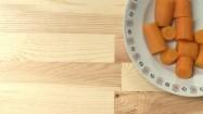 Pokrojone kawałki marchewki na talerzu i słoik miodu