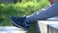 Chłopak ze smartfonem siedzący na schodkach