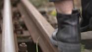 Mężczyzna idąca po torach kolejowych